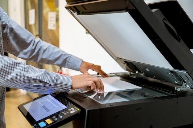 Geschäftsmann handpresseknopf auf platte des druckers, druckerscannerlaser-bürokopiermaschinenversorgungsanfang