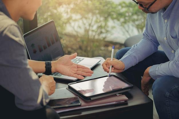 Geschäftsmann hat einen digitalen bleistift bekommen, um nach verhandlungen mit geschäftspartnern bei einem geschäftstreffen den digitalen vertrag zu unterschreiben