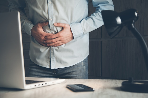 Geschäftsmann hat magenschmerzen im arbeitszimmer