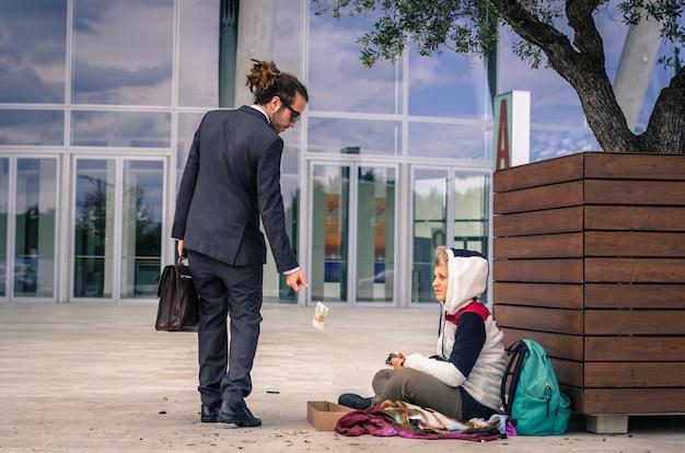 Geschäftsmann hilft einem obdachlosen, der geld gibt - geschäfts-, menschen- und lebensstilkonzept - kaukasier