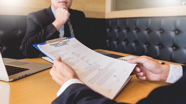 Geschäftsmann hören auf den jungen attraktiven mann, der über seine profilkandidaten-interviewantworten erklärt