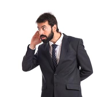 Geschäftsmann hört über isolierten weißen hintergrund