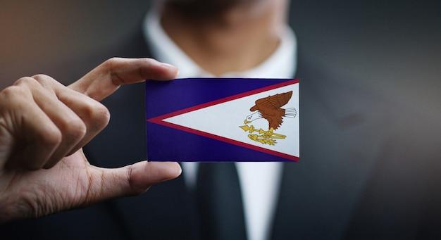 Geschäftsmann holding card von amerikanisch-samoa-flagge