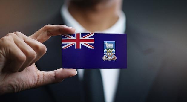Geschäftsmann holding card von falkland islands flag