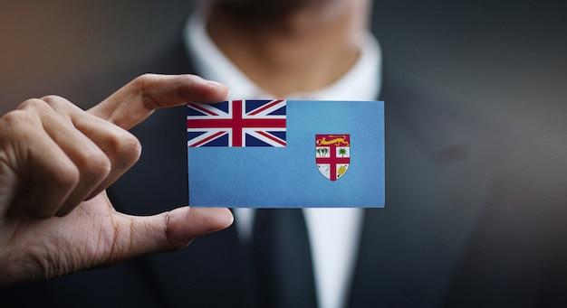 Geschäftsmann holding card von fidschi flagge