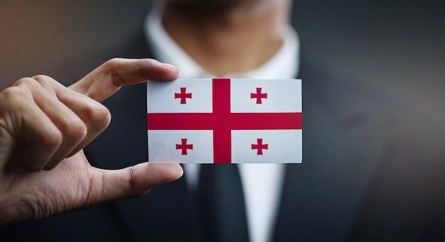 Geschäftsmann holding card von georgia flag