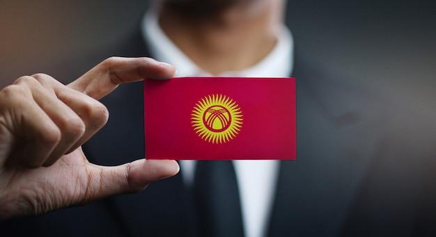 Geschäftsmann holding card von kirgisistan flagge