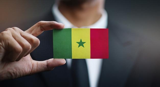 Geschäftsmann holding card von senegal flagge