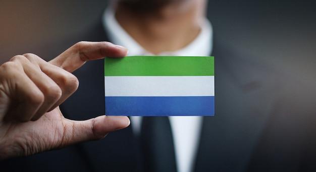 Geschäftsmann holding card von sierra leone flag