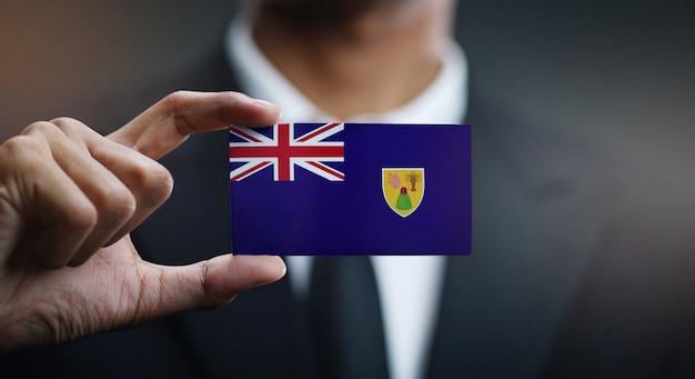 Geschäftsmann holding card von turks- und caicosinseln flagge
