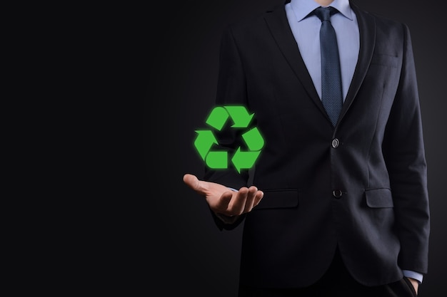 Geschäftsmann im anzug auf dunklem hintergrund hält ein recycling-symbol, zeichen in seinen händen. ökologie, umwelt und naturschutzkonzept. neonrotes blaues licht
