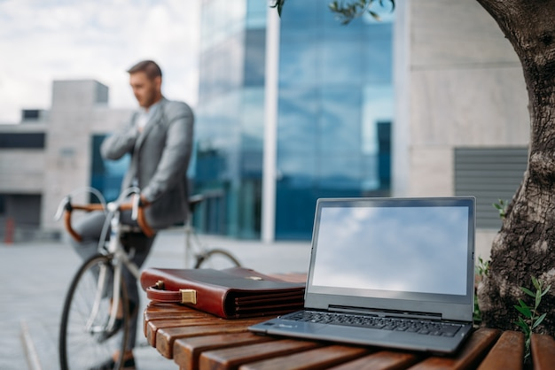 Geschäftsmann im anzug auf fahrrad in der innenstadt, glasgebäude auf hintergrund. geschäftsperson, die auf öko-transport auf stadtstraße reitet
