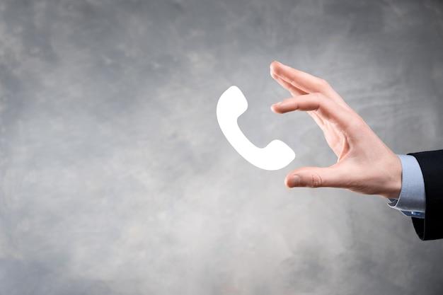 Geschäftsmann im anzug auf schwarzem hintergrund halten telefonsymbol. rufen sie jetzt business communication support center kundendienst-technologie-konzept an.
