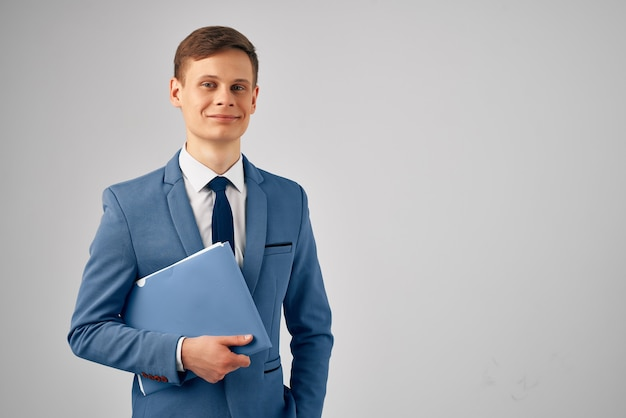 Geschäftsmann im anzug blaue ordnerdokumente arbeiten professionell. foto in hoher qualität