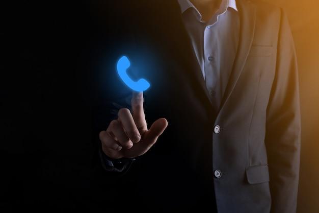 Geschäftsmann im anzug, der auf blaues telefonsymbol klickt