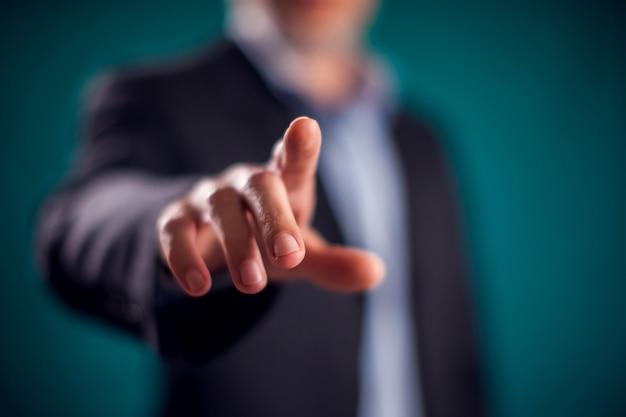 Geschäftsmann im anzug, der den virtuellen knopf berührt oder auf etwas zeigt