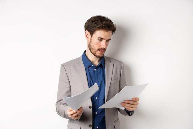 Geschäftsmann im anzug, der durch papiere schaut, dokumente bei der arbeit liest, beschäftigt auf weißem hintergrund steht.