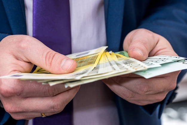 Geschäftsmann im anzug, der euro-banknoten zählt, nahaufnahme