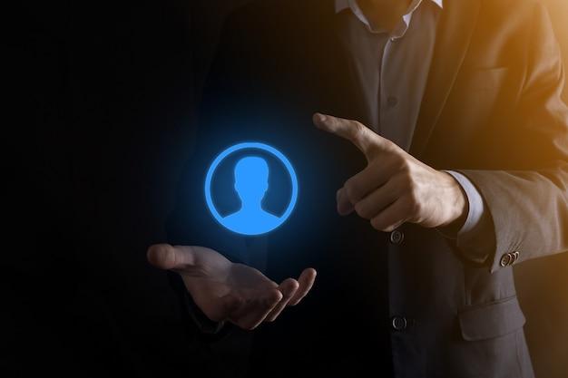 Geschäftsmann im anzug, der handsymbol des benutzers heraushält. vordergrund der internet-symbole.