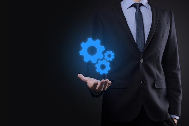 Geschäftsmann im anzug, der metallzahnräder und zahnradmechanismus hält, das interaktions-teamarbeitskonzept darstellt, handhaltegruppe des virtuellen zahnrads.
