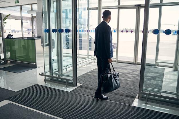 Geschäftsmann im anzug, der mit einem lederkoffer in der hand durch die eingangshalle geht