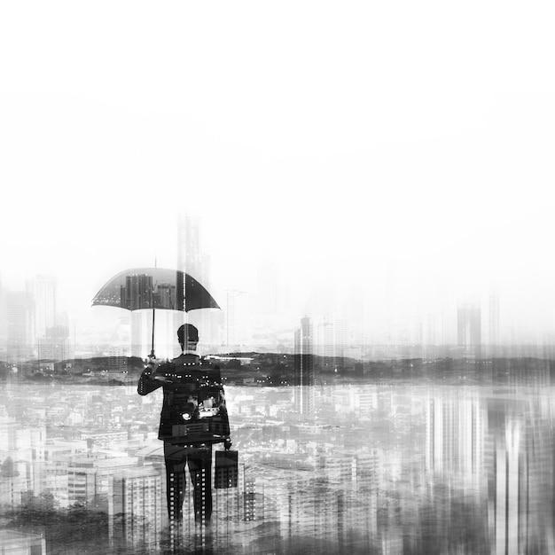 Geschäftsmann im anzug, der regenschirm auf stadthintergrund hält