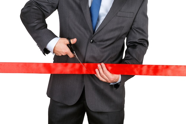 Geschäftsmann im anzug, der rotes band mit einer schere schneidet