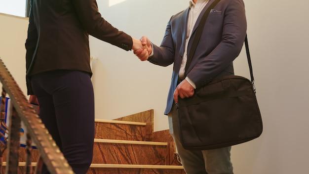Geschäftsmann im anzug händeschütteln mit kollegin auf der bürotreppe, während er in der finanzgesellschaft diskutiert. gruppe professioneller geschäftsleute, die an einem modernen finanzarbeitsplatz arbeiten.