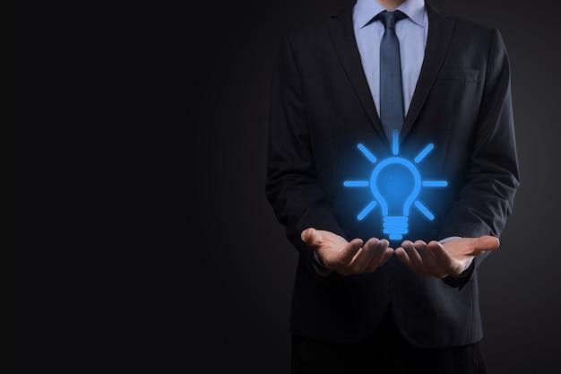 Geschäftsmann im anzug mit einer glühbirne in den händen. hält ein leuchtendes ideensymbol in der hand