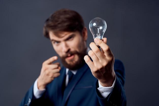 Geschäftsmann im anzug mit einer lampe in den händen kreativität