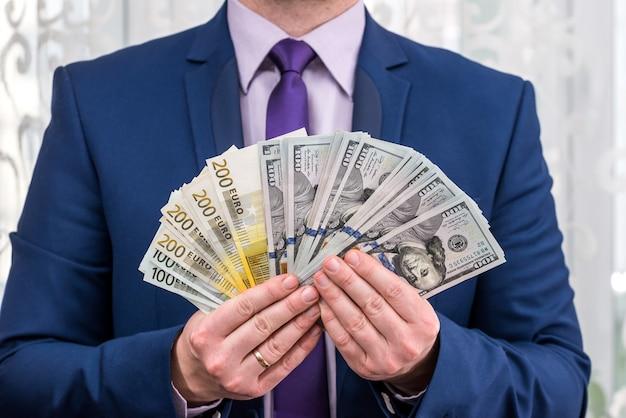 Geschäftsmann im anzug mit euro- und dollar-fan