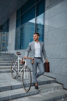 Geschäftsmann im anzug mit fahrrad kommt die treppe im bürogebäude in der innenstadt herunter.