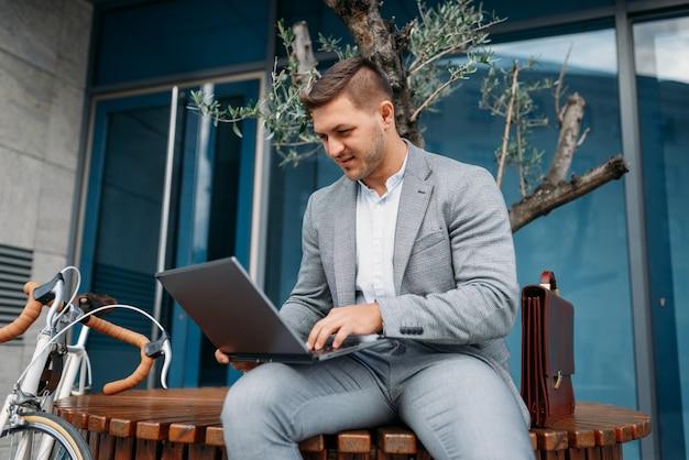 Geschäftsmann im anzug mit laptop und fahrrad in der innenstadt, glasgebäude auf hintergrund. geschäftsperson, die auf öko-transport auf stadtstraße reitet