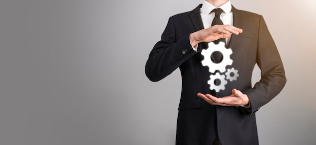 Geschäftsmann im anzug mit metallzahnrädern und zahnrädern, die das konzept der interaktionsteamarbeit darstellen, hand halten gruppe virtueller zahnräder.