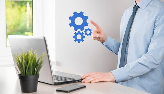 Geschäftsmann im anzug mit metallzahnrädern und zahnrädern, die das konzept der interaktionsteamarbeit darstellen, hand halten gruppe virtueller zahnräder