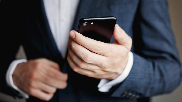 Geschäftsmann im anzug mit smartphone. mann halten telefon.