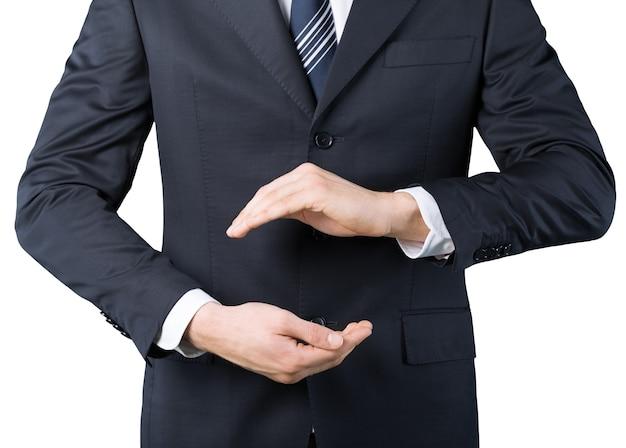 Geschäftsmann im anzug mit zwei händen in position, um etwas zu schützen
