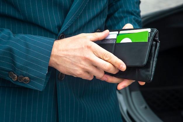 Geschäftsmann im anzug öffnet seine business-leder-geldbörse nahaufnahme. finanzen und wohlstand in der wirtschaft