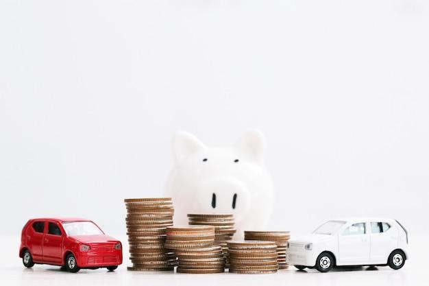 Geschäftsmann im anzug offene hand stützen umarmungsmodell des spielzeugautos auf über viel geld des gestapelten münzversicherungsdarlehens und des kaufautofinanzierungskonzepts. sparschwein sparen