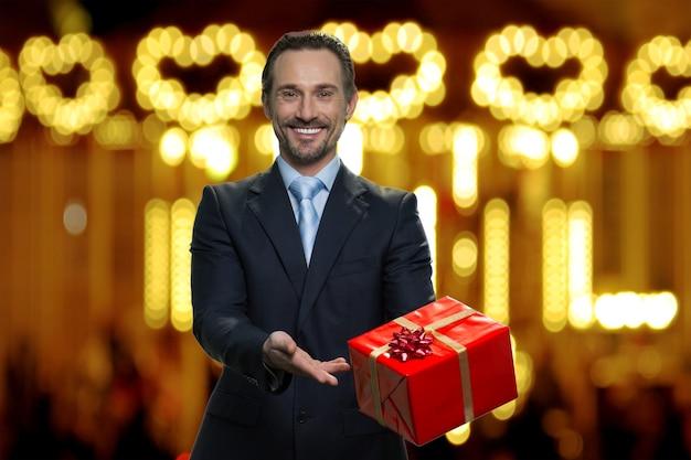 Geschäftsmann im anzug präsentiert große rote geschenkbox. geschenk zu weihnachten. unscharfer beleuchteter hintergrund.