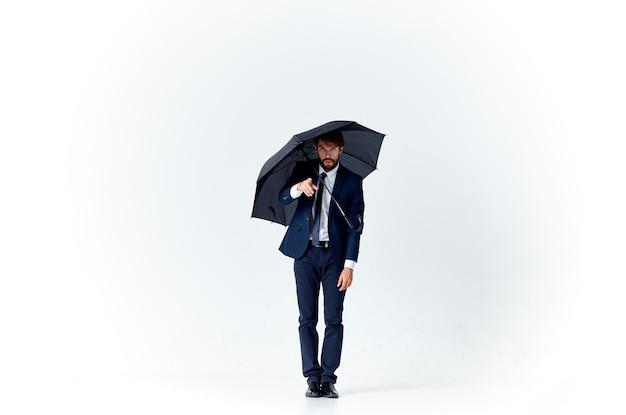 Geschäftsmann im anzug regenschirm schutz selbstbewusstsein studio. foto in hoher qualität