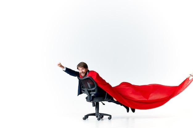Geschäftsmann im anzug reitet auf einem stuhl mit einem roten mantel-superhelden-manager