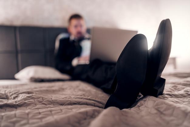 Geschäftsmann im anzug sitzt auf dem bett im hotelzimmer und benutzt laptop für arbeit. überarbeitungskonzept. selektiver fokus auf schuhe.