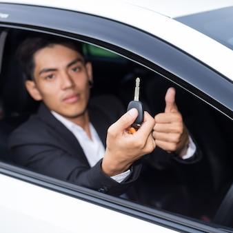 Geschäftsmann im anzug und hält einen autoschlüssel in der hand
