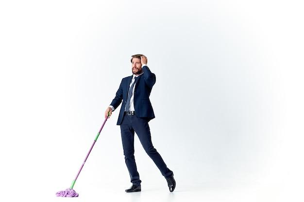 Geschäftsmann im anzug wäscht die böden mit einem mopp-manager