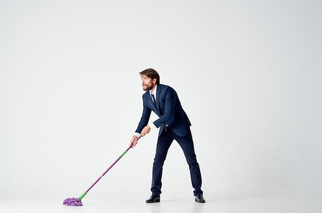 Geschäftsmann im anzug wäscht die böden mit einem mopp-reinigungsbüroleiter