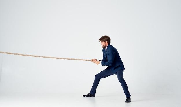 Geschäftsmann im anzug zieht den hellen hintergrund des seilstudios