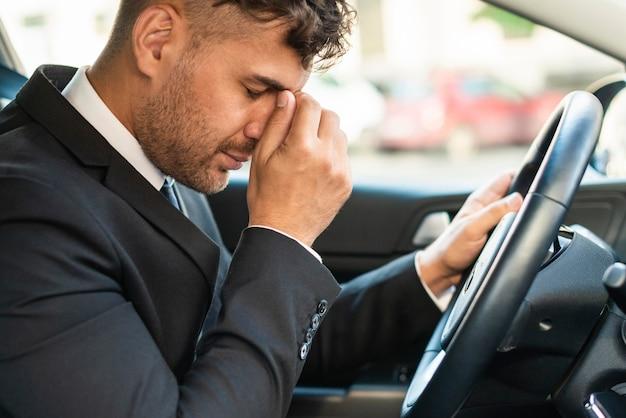 Geschäftsmann im auto, das im verkehr stecken bleibt
