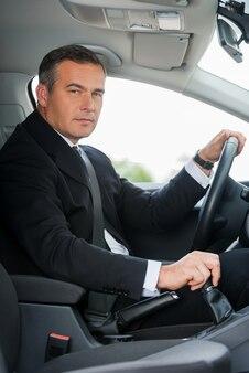 Geschäftsmann im auto. seitenansicht eines selbstbewussten reifen geschäftsmannes, der auto fährt und sie ansieht