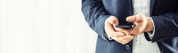 Geschäftsmann im blauen anzug, der ein schwarzes smartphone in den händen hält und mit kollegen plaudert.